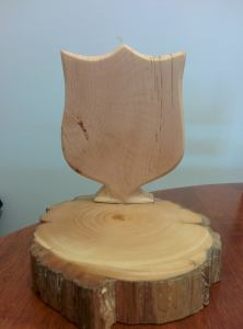 Picture of wooden sculpture - a Salvation Army Shield carved from Huon Pine on a disc of Huon Pine. Made by Ben Clapton