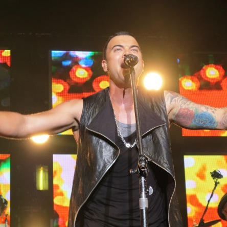 Guy Sebastian standing infront of a microphone singing with his arms outstreatched. He is wearing a black singlet and a grey singlet, with a black leather sleeveless jacket that is unzipped.